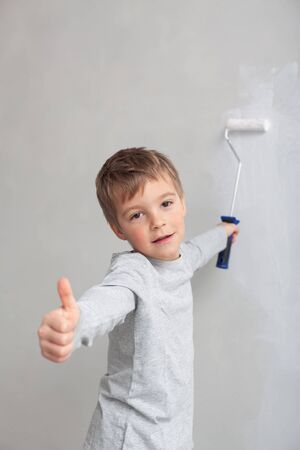 Little boy while painting the walls in the room. Archivio Fotografico - 146462695
