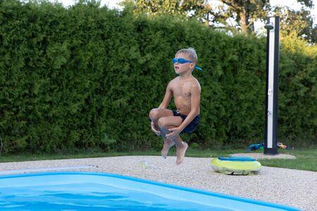Boy jumping into the water. Archivio Fotografico - 146462756