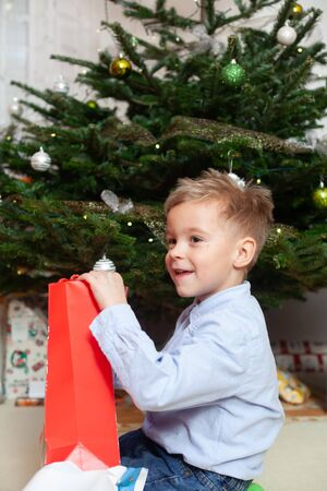The child rejoices in unwrapping Christmas presents. Christian tradition. Archivio Fotografico - 146462760