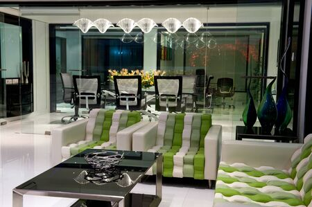 Interior of modern office Waiting room with glass walls, lounge with armchairs and mix furniture.