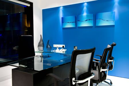 Modern manager office interior with a Blue walls, a stylish table, chairs and Painting. Imagens