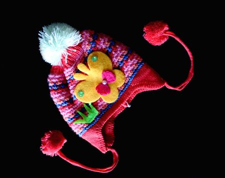 Little baby colorful woolen cap with fur pompon ball and butterfly isolated on black - Image Foto de archivo