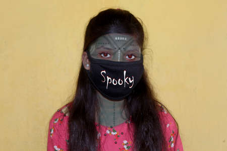 spooky witch women in halloween costume with wear mask on face on a celebration of Halloween Day of the dead make up during covid-19, corona virus