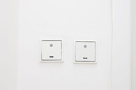 switches: two plastic light switches on white wall