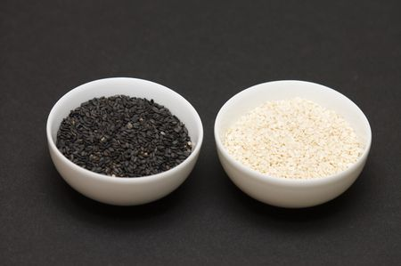 black and white sesame seeds in a bowl on dark background Stock Photo