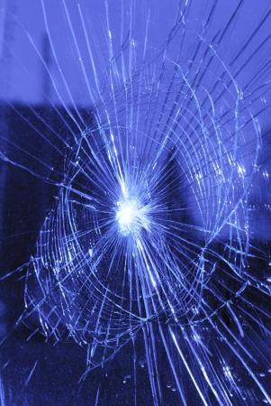 ventana rota: ventana rota con grietas en forma de red Foto de archivo