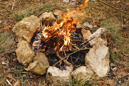 camping - burning wood on small campire surrounded by stones photo
