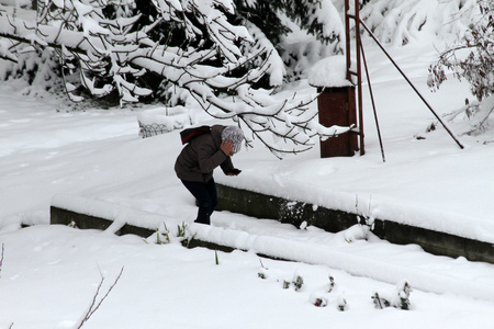 Person walks hard on a snowy icy sidewalk when snow fell and hits her on head after a heavy snowfall in the city of Sofia, Bulgaria
