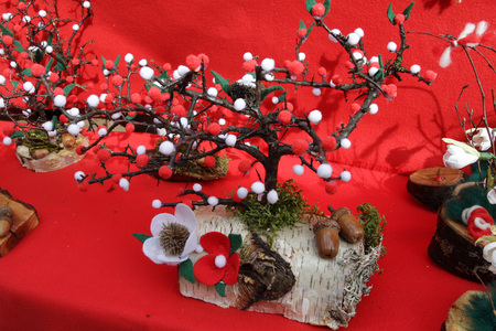 Red and white Martenitsi on outdoor market for martenici. Martenitsa or martenitza is given on 1st March as a symbol of health and prosperity. Red and white threads for health. Wooden handmade tree with red and white treads