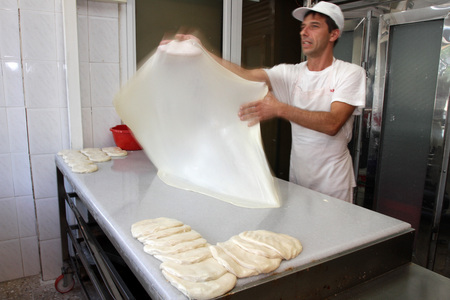 A baker knead dough for pizza with roller and flour in bakery in the city of Sofia, Bulgaria – sep 4 , 2015. Focus on pizza dough, not post process, pictures taken in motion