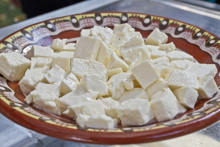 Little chopped cubes of white brine cheese from cow, goat or sheep milk ready for eating in traditionally decorated ceramic plate. White brine bulgarian sirene ready for consummation.
