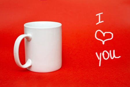 "White mug on red background with sign "" I love you"". Copy space for writing. White glass isolated. St. Valentine's day concept. February 14 concept"