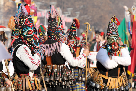 """Kukeri , mummers perform rituals intended to scare away evil spirits during the international festival  of masquerade games """"Surva"""" in Pernik, Bulgaria – Jan27,2018. Mummers walk and dance with costumes and big huge bells."""