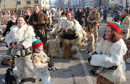 "Women Kukeri , mummers perform rituals intended to scare away evil spirits during the international festival  of masquerade games ""Surva"" in Pernik, Bulgaria – Jan27,2018. Mummers walk and dance with costumes and big huge bells. biên tập"
