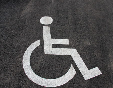 Handicap icon. Parking lot with handicap sign and symbol. Empty handicapped reserved parking space with wheelchair symbol. Disabled person sign. Copy space.