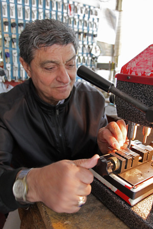 Locksmith in workshop makes new key in Sofia, Bulgaria – sept 9, 2015. Professional making key in locksmith. Person who makes and repairs keys and locks. Key maker Machine and Accessary. Standard-Bild - 105179405