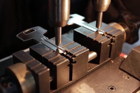 Cerrajero en taller hace nueva llave. Profesional haciendo llave en cerrajería. Persona que fabrica y repara llaves y cerraduras. Máquina para hacer llaves y accesorios.