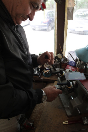 Locksmith in workshop makes new key in Sofia, Bulgaria – sept 9, 2015. Professional making key in locksmith. Person who makes and repairs keys and locks. Key maker Machine and Accessary Standard-Bild - 98326761