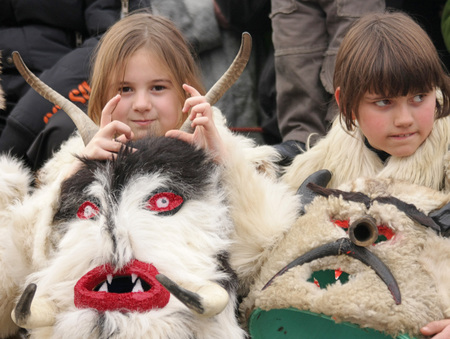 "Girls Kukeri, kids mummers perform rituals with costumes and big bells, intended to scare away evil spirits on international festival of masquerade games ""Surva"" in Pernik, Bulgaria – Jan24,2009. Carnival"