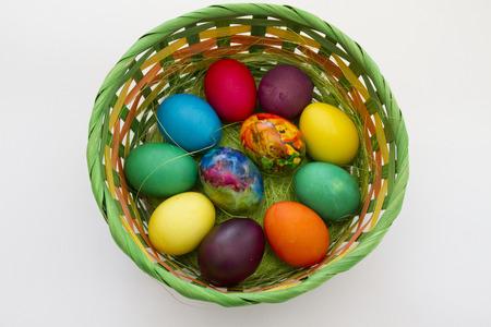 Easter eggs. Handmade painted eggs in basket for Easter celebration isolated on white background. Easter. Colored Easter eggs. Colorful egg. Copy space. Text space. Unique handmade painted eggs.