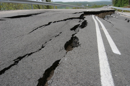 Road collapses with huge cracks. International road collapsed down after bad construction. Damaged Highway Road. Asphalt road collapsed and fallen. Erosion.