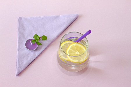 Glass of water, lemon and mint, and candle. Glass of pure water and fresh organic lemon and mint isolated on purple background. Detox and healthy food concept. Stock Photo