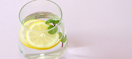 Glass of water, lemon and mint. Glass of pure water and fresh organic lemon and mint isolated on purple background. Detox and healthy food concept