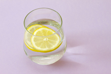 Glass of water and lemon. Glass of pure water and fresh organic lemon isolated on purple background. Detox and healthy food concept. Boost your metabolism concept
