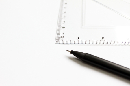 Mathematical accessories. Triangle ruler for math and black pen for school on a white background. School supplies. Office supplies for work or study. Geometric pattern. Math.