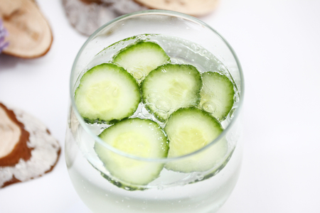 Detox flavored water with cucumber on white background with wood decoration. Healthy food concept.  Refreshing summer homemade cocktail. Copy space. No sharpen. Anti stress drink. Stock Photo