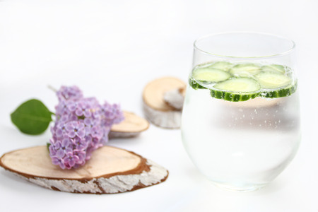 Detox flavored water with cucumber on white background with lilac and wood decoration. Healthy food concept.  Refreshing summer homemade cocktail. Copy space. No sharpen. Anti stress drink.
