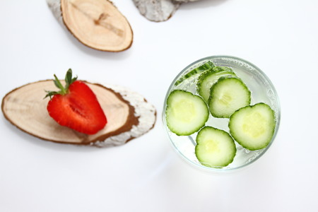 Detox flavored water with cucumber on white background with red strawberry and wood decoration. Healthy food concept.  Refreshing summer homemade cocktail. Copy space. No sharpen. Anti stress drink.