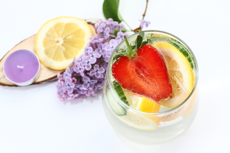Detox flavored water with lemon, cucumber and  strawberry on white background with lilac and wood decoration. Healthy food concept.  Refreshing summer homemade cocktail. Copy space. No sharpen.