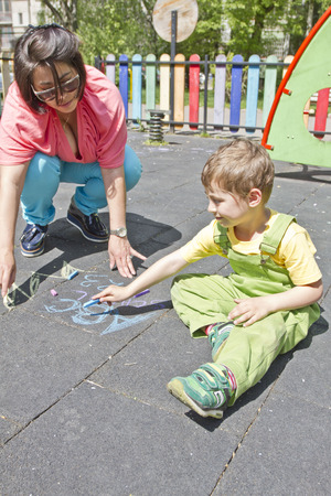 Mom and cute boy draw with colorful chalks on asphalt. Summer activity and creative games for small kids. Quality family time. Happy mother's day. Mother and child together having fun. Archivio Fotografico