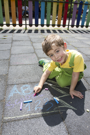 Cute boy write with colored chalks. Little kid draws with chalks. School, ABC letters and 123 sigh written with colored chalks. Vacation concept. Education concept. School and fun time. Play and game time.  No sharpen. Banque d'images
