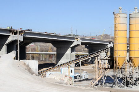 New highway under construction. A new bridge freeway made of concrete and metal to pass traffic from big city. An unfinished interstate bridge. Road under construction. Overpass road  in progress  with cranes and concrete mixer. Stock Photo