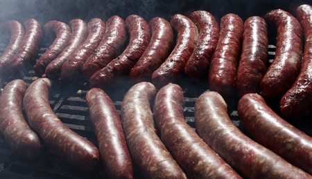 Sausages on a grill. Bratwurst on a barbecue. BBQ. Grilled sausages on bbq. Roasted meat sausages on a barbeque. Fast food outdoor on a grill. Natural light. cholesterol Stock Photo