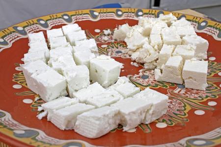 White brine cheese. Feta cheese. Farm made cheese pieces in a plate. Gourmet bites. Cover photo.
