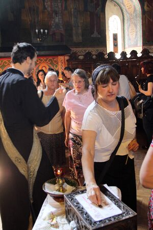 Woman gives donations to the church after being anointed by the priest in the liturgy in a church in Sofia, Bulgaria on august 15, 2012.