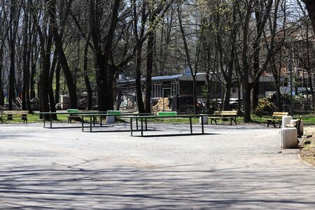 Empty park with empty benches as prevention from coronavirus Covid-19 disease. Closed park for restriction during quarantine.