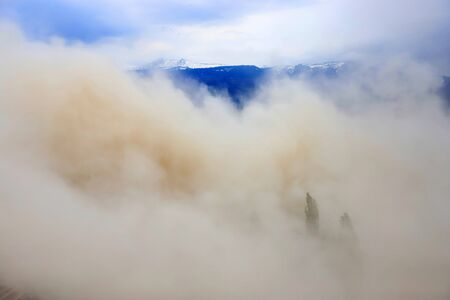 Heavy air pollution. Extremely polluted air with mountain as background. Cloud of dust.