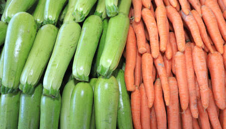 Fresh organic green zucchini and carrots on daylight. Vegetables pattern.