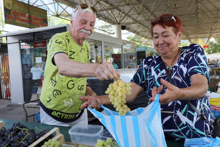 Sofia, Bulgaria on September 16, 2020: People buy grapes at a farmer's market.