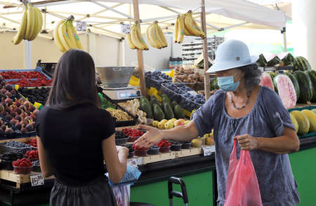 Sofia, Bulgaria on September 16, 2020: Old woman wearing protective face mask is buying fruits at a market.