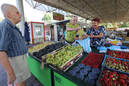Sofia, Bulgaria on September 16, 2020: Elderly people buy grapes at a farmer's market.