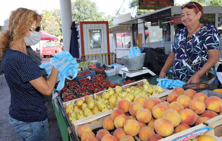 Sofia, Bulgaria on September 16, 2020: Woman wearing protective face mask is buying fruits at a market.