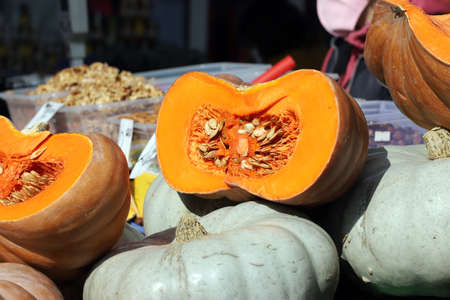 Sliced and whole pumpkins , with seeds, at the market for Halloween and Thanksgiving