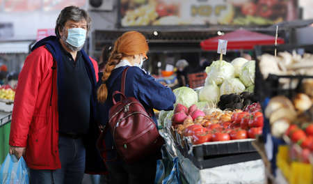 People are wearing face masks buy fresh fruits and vegetables on a farmer market in Sofia, Bulgaria on nov 09, 2020