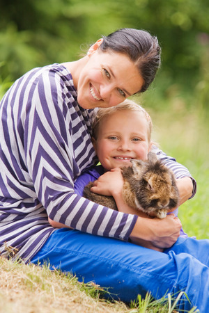 daugther: The mother having fun with her daugther. Isolated on green grassy background. The concept of happiness is having children.