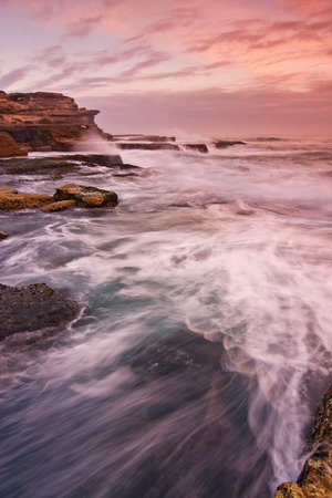 ocean waves: Sunrise landscape of ocean with waves clouds and rocks Stock Photo